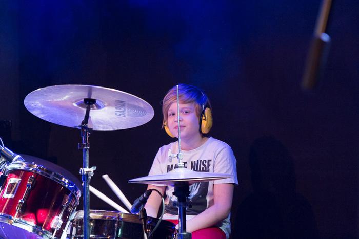 Op de foto zit een jonge drummer achter zijn drumstel