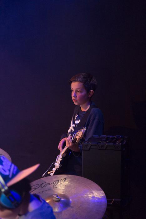Op de foto een jonge gitarist die de situatie even tot zich laat doordringen, en daarna klaar is om te gaan spelen.