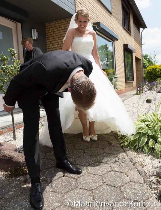 De bruidegom tilt de jurk van de bruid op om de schoenen te bekijken