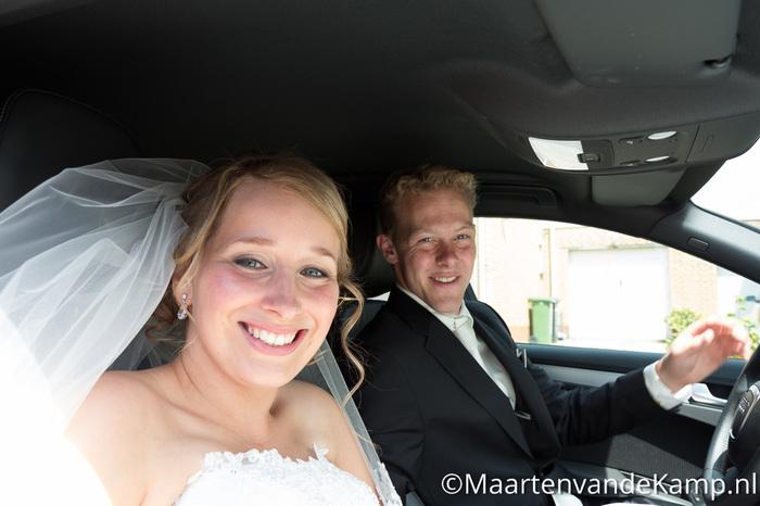 De bruid en bruidegom in de auto