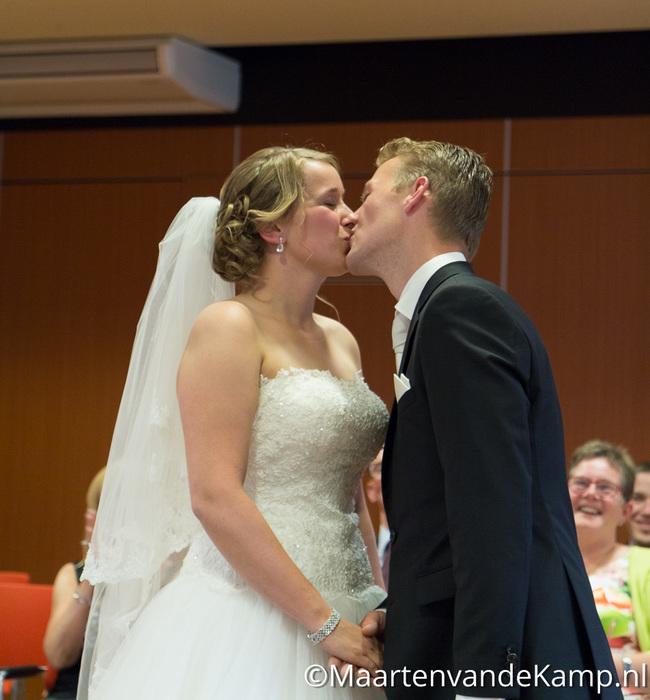 De bruid en bruidegom kussen elkaar
