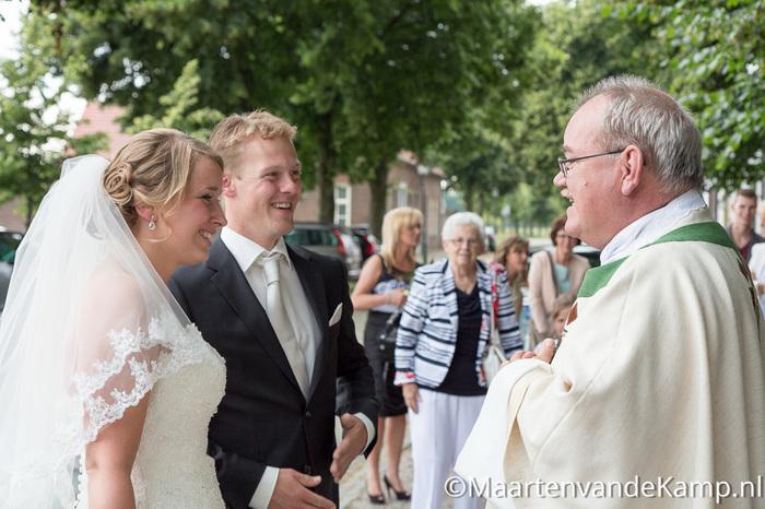 De bruid en bruidegom worden door de pastoor bij de kapel ontvangen