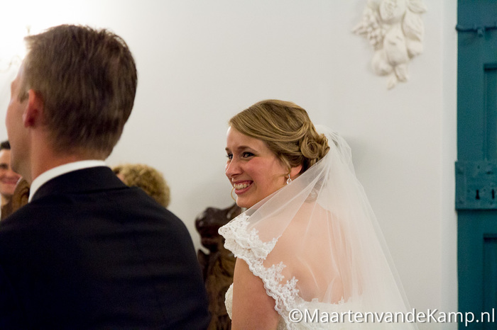 De bruid lacht naar de bruidegom in de kapel