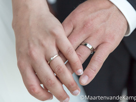 De hand van de bruid en de bruidegom, met de trouwringen