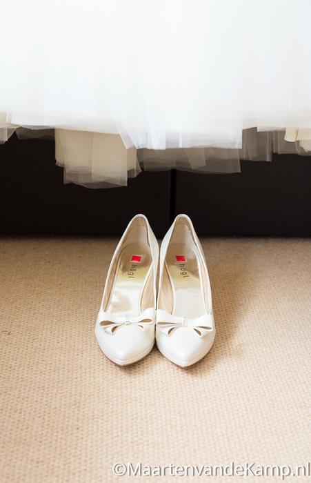 De schoenen van de bruid onder de jurk